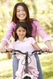 Aziatische moeder en dochter op fiets in park Stock Afbeeldingen