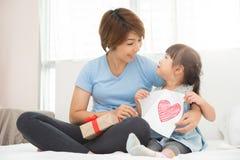 Aziatische moeder en haar dochter die een prentbriefkaar houden stock afbeelding