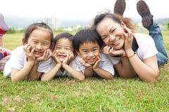 Aziatische moeder en haar kinderen op het groene gebied stock foto