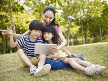 Aziatische moeder en kinderen die tabletcomputer met behulp van Royalty-vrije Stock Foto's