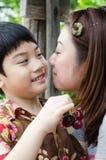 Aziatische moeder met haar zoonskers op hand Stock Afbeeldingen