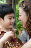 Aziatische moeder met haar zoonskers op hand Royalty-vrije Stock Afbeeldingen