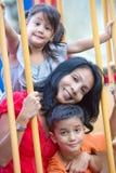 Aziatische moeder met twee jonge kinderen bij speelplaats royalty-vrije stock foto