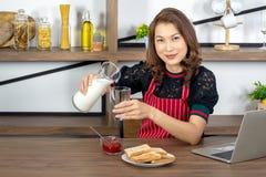 Aziatische mooie bedrijfsvrouwen die melk gieten royalty-vrije stock foto's