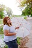 Aziatische mooie vette vrouw met paraplu in de tuin Royalty-vrije Stock Foto's