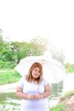 Aziatische mooie vette vrouw met paraplu in de tuin Stock Afbeeldingen