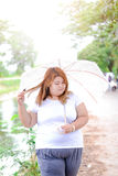 Aziatische mooie vette vrouw met paraplu in de tuin Royalty-vrije Stock Foto
