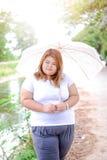 Aziatische mooie vette vrouw met paraplu in de tuin Stock Afbeelding