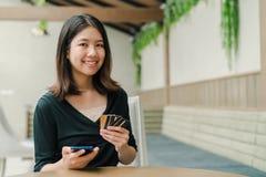 Aziatische mooie vrouw die een zwarte overhemdszitting in het huis dragen is Er een creditcard in uw hand en u houdt de telefoon stock fotografie