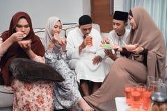 Aziatische moslimfamilie die ??n of andere snack en drank hebben samen stock foto's