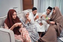Aziatische moslimfamilie die ??n of andere snack en drank hebben samen stock foto