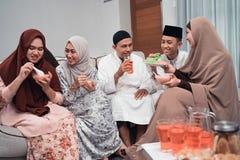 Aziatische moslimfamilie die ??n of andere snack en drank hebben samen stock afbeelding