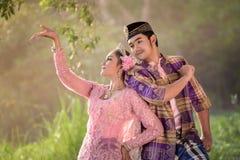 Aziatische Moslimman en vrouw die traditionele kleding dragen stock foto's