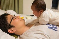 Aziatische nieuw - het geboren baby spelen op father& x27; s borst Stock Afbeeldingen