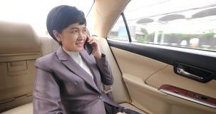 Aziatische onderneemster in de auto die een telefoongesprek maken stock videobeelden