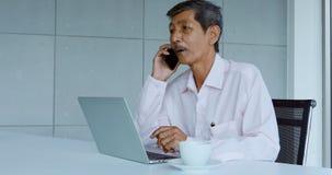 Aziatische onderneemster die laptop in bureau met behulp van stock videobeelden