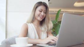 Aziatische onderneemster die laptop computer, het glimlachen met behulp van stock afbeelding