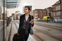 Aziatische onderneemster die met haar bagage bij een trameinde wachten royalty-vrije stock foto's