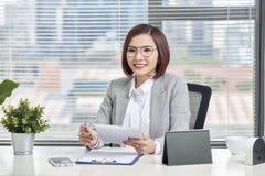 Aziatische onderneemster die met tabletcomputer bij bureau werken royalty-vrije stock afbeelding