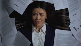 Aziatische onderneemster die met verschrikking stapel van documenten bekijken, zware baanclose-up stock videobeelden