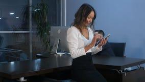Aziatische onderneemster die smartphone in bureau gebruiken stock foto