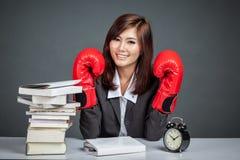 Aziatische onderneemster met bokshandschoen, boeken en klok Royalty-vrije Stock Afbeelding
