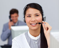 Aziatische onderneemster met hoofdtelefoon bij haar bureau Royalty-vrije Stock Fotografie