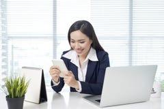 Aziatische onderneemsterzitting door bureau met laptop en gebruiken mobiel in bureau royalty-vrije stock fotografie