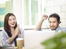 Aziatische ondernemers die succes en voltooiing in bureau vieren stock afbeelding