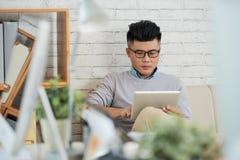 Aziatische ontwerper die tablet op bank gebruiken royalty-vrije stock afbeelding