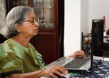 Aziatische oude vrouw die computer met behulp van Royalty-vrije Stock Foto's