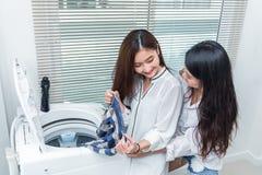 Aziatische paarvrouwen die huishoudelijk werk en karweien voor wasmachine samen doen en kleren in wasserijruimte laden Mensen en stock afbeeldingen