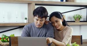 Aziatische paarzitting en samen het gebruiken van laptop