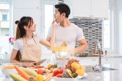 Aziatische paren die voedsel samen in keuken voeden Mensen en lifes royalty-vrije stock fotografie