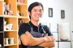 Aziatische Pottenbakker in zijn winkel verkopende herinneringen Royalty-vrije Stock Afbeelding
