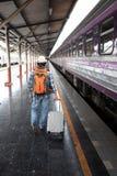 Aziatische reizigersmens die met bezittingen op reis door trein bij Chiang Mai-station, Thailand wachten stock fotografie