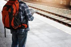 Aziatische reizigersmens die met bezittingen op reis door trein bij Chiang Mai-station, Thailand wachten stock foto