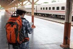 Aziatische reizigersmens die met bezittingen op reis door trein bij Chiang Mai-station, Thailand wachten royalty-vrije stock afbeelding