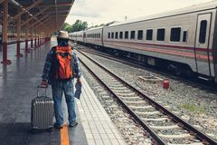 Aziatische reizigersmens die met bezittingen op reis door trein bij Chiang Mai-station, Thailand wachten royalty-vrije stock afbeeldingen