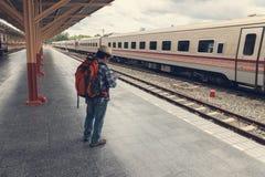 Aziatische reizigersmens die met bezittingen op reis door trein bij Chiang Mai-station, Thailand wachten stock foto's