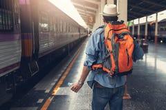 Aziatische reizigersmens die met bezittingen op reis door trein wachten stock fotografie