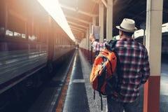 Aziatische reizigersmens die met bezittingen op reis door trein wachten stock foto's