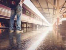 Aziatische reizigersmens die met bezittingen op reis door trein a wachten stock foto