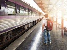 Aziatische reizigersmens die met bezittingen op reis wachten Stock Fotografie
