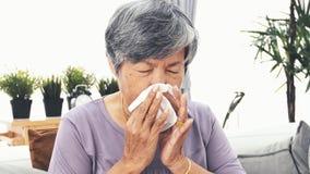 Aziatische Rijpe vrouw met allergie die en haar neus in een weefsel, de langzame motie van 4K blazen niezen stock footage