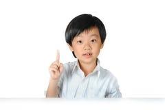 Aziatische schooljongen die zijn wijsvinger opheft Royalty-vrije Stock Foto's