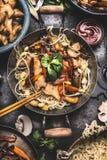Aziatische schotel met de noedel be*wegen-gebraden gerecht van kippengroenten in weinig wok met eetstokje en kokende ingrediënten stock foto's