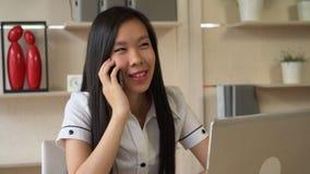 Aziatische secretaresse of manager in eigentijds bureau die op de mobiele telefoon met cliënt spreken stock videobeelden