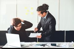 Aziatische Slechte boze werkgever die bij bedrijfsmensen droevige gedeprimeerde emplo schreeuwen stock foto