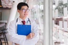 Aziatische slimme gekruiste artsen bevindende wapens stock afbeelding